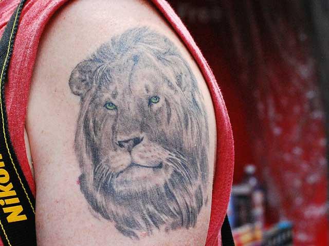 Eine Tätowierung in Form eines Löwen Kopfes - sehr künstlerisch.